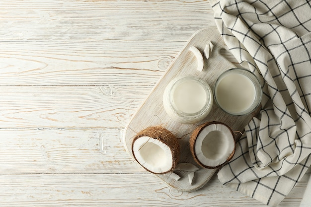 Board with fresh coconut and coconut milk on wooden
