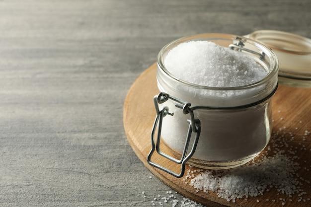 灰色のテーブルに塩のガラス瓶とボード