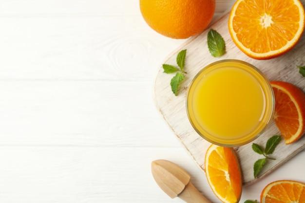 Доска со стаканом апельсинового сока, апельсинов и соковыжималкой на деревянном столе