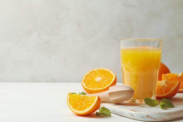 木製のテーブルにオレンジジュース、オレンジ、ジューサーのガラスとボード
