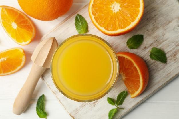 Доска со стаканом апельсинового сока, апельсинов и соковыжималкой на деревянном