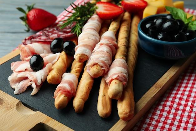 Доска с гриссини и закусками на деревянных фоне