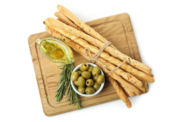 Доска с гриссини, оливками и маслом, изолированные на белом фоне