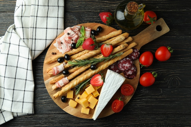 Board with grissini and snacks on wooden surface