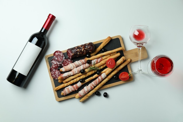 Board with grissini sticks with bacon, snacks and wine on white surface