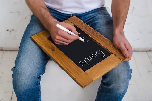 新しい目標を掲げた委員会。新しい目標を入力してください。木のフレームの黒い黒板にチョークで碑文。