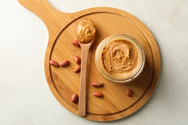 Board with peanut, spoon and jar with peanut butter on white background