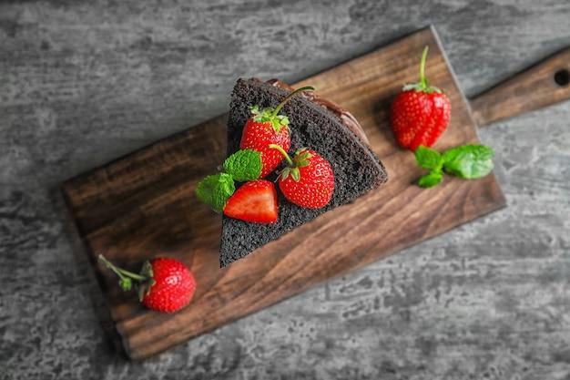 Доска с кусочком вкусного шоколадного торта на столе
