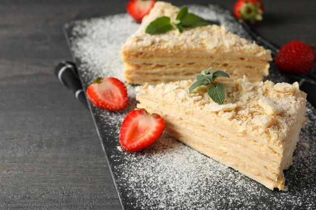 Доска с кусочками торта наполеон с клубникой