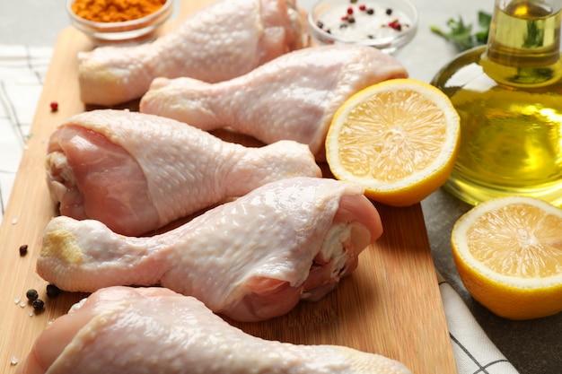 Доска с сырым куриным мясом на сером пространстве. готовить курицу