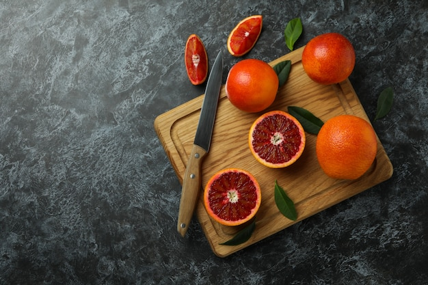 Board with red oranges, leaves and knife on black smoky table