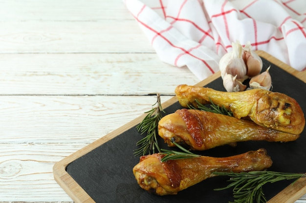 Board with roast chicken drumsticks, space for text