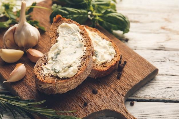 Доска с кусочками свежего хлеба и чесночного масла на светлом деревянном фоне