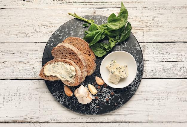 Доска с кусочками свежего хлеба, чесночного масла и ингредиентов на светлом деревянном фоне