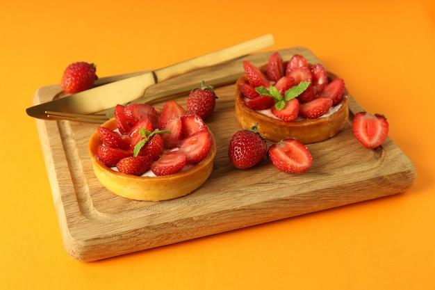 Board with strawberry tarts on orange background.