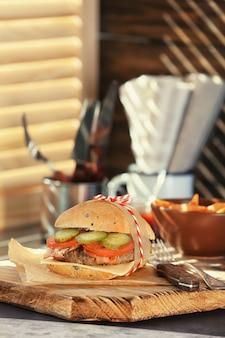 Доска с вкусным гамбургером с беконом на столе