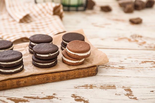 Доска с вкусным шоколадным печеньем на белом столе