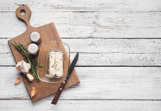 Доска с вкусным чесночным маслом и ингредиентами на светлом деревянном фоне