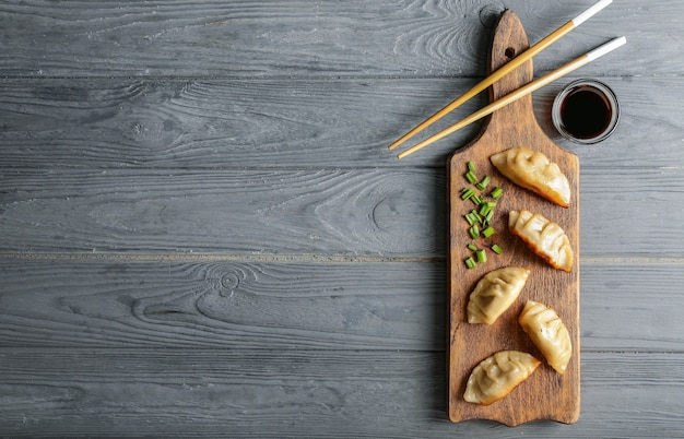 Board with tasty japanese gyoza on wooden table