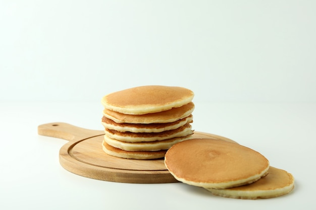 Board with tasty pancakes on white table
