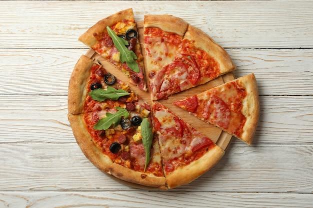 Доска с вкусной пиццей на белом деревянном столе