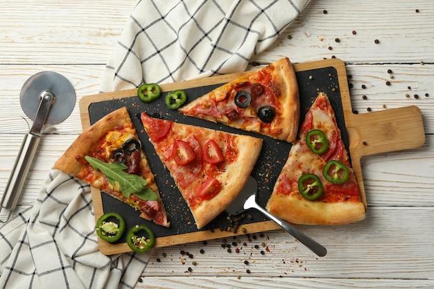 Доска с кусочками вкусной пиццы на белом деревянном столе