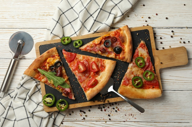 Board with tasty pizza slices on white wooden table
