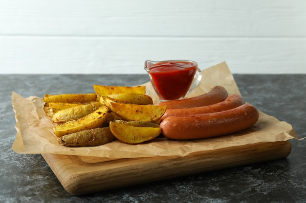 Board with tasty potato wedges, sauce and sausage
