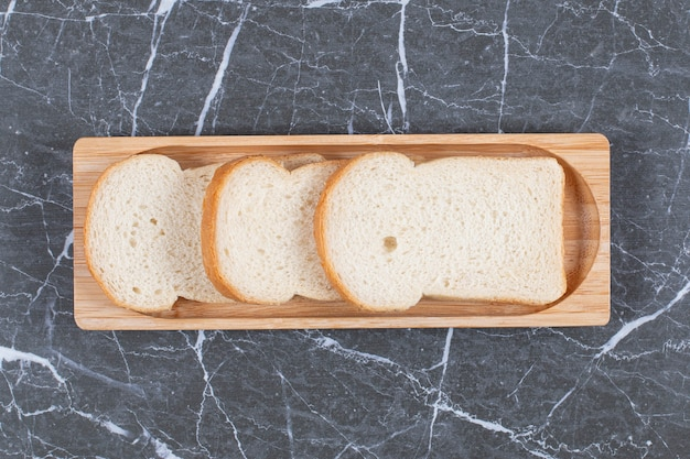 Board with tasty toasted bread, on the marble surface
