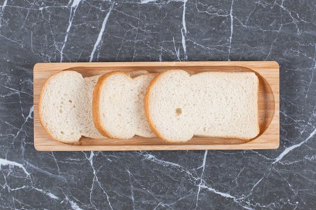 Доска с вкусным поджаренным хлебом, на мраморной поверхности