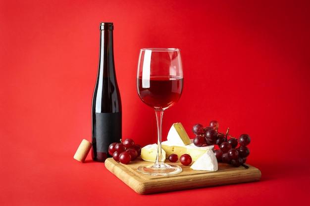 빨간색 배경에 와인, 치즈, 포도를 넣은 보드