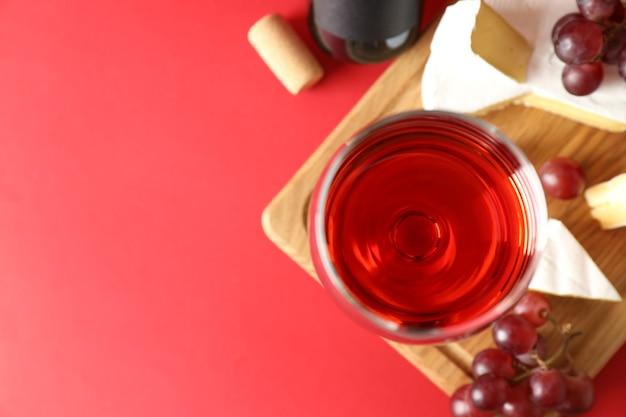 赤の背景にワイン、チーズ、ブドウとボード