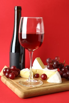 Board with wine, cheese and grape on red background