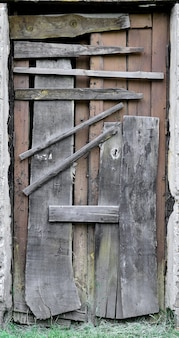 Boarded up wooden door to an old abandoned house