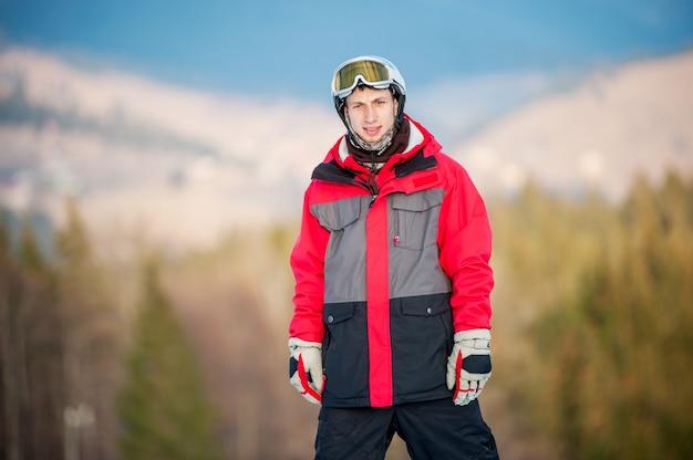 Boarder wearing helmet, skiing glasses, gloves, ski suit.