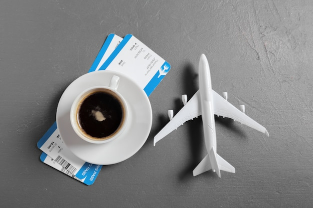 Boarding pass and toy airplane on table top view
