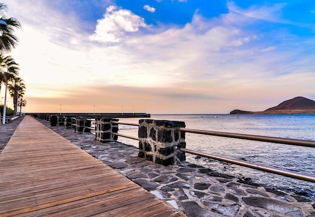 Boardwalk by the sea under a beautiful cloudy sky in the canary islands, spain