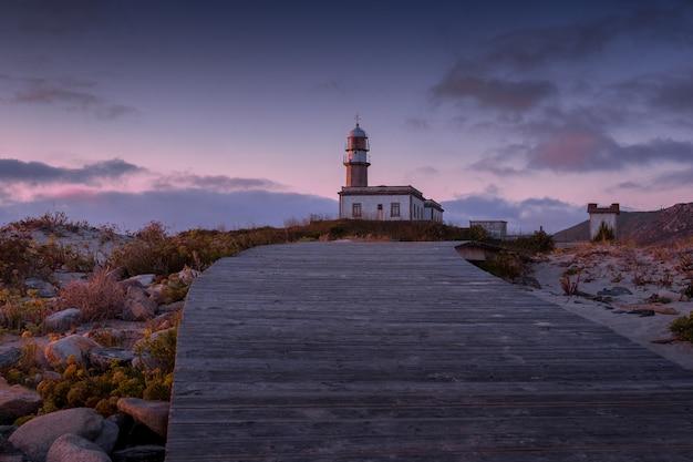 Променад, ведущий к маяку ларино во время заката вечером в испании