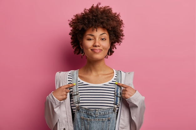 Boastful curly afro american woman got good job, points at herself
