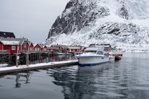 Boat anchored on pier with fishing village in lofoten