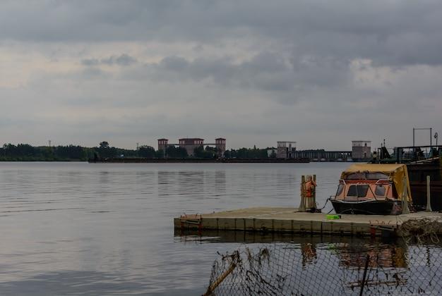 부두에서 보트를 타고 리빈스크 관문과 배경 강의 리빈스크 수력 발전소...
