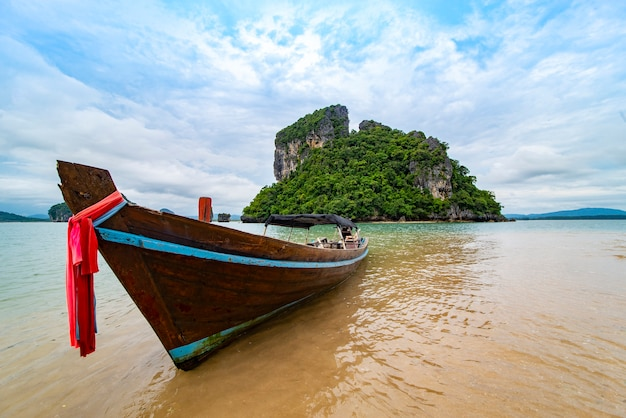 Boat on the beach and background rock island landscape in the southern tip of thailand.