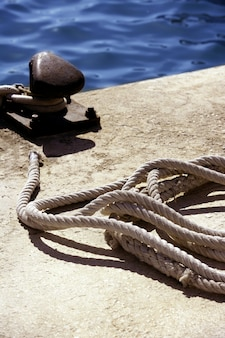 Boat bollard, ropes and knots in mediterranean harbor