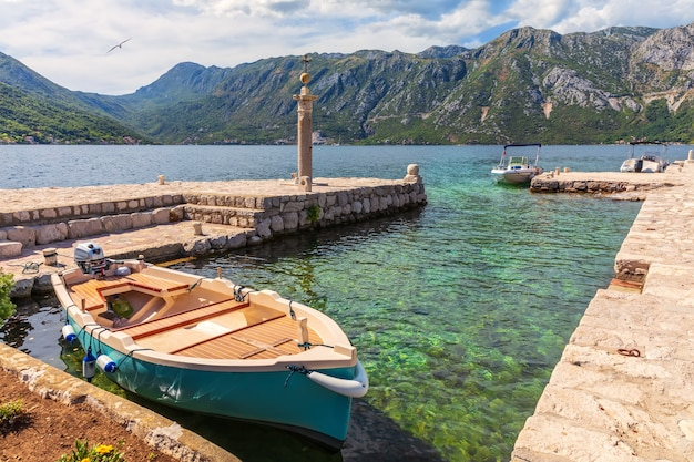 Boat by the pier of the our lady on the rock island near perast, montenegro.