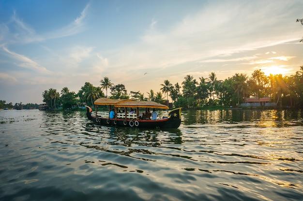 Лодка с туристами плывет по реке на фоне пальм и красивого заката. солнце садится за горизонт и сияет сквозь пальмы