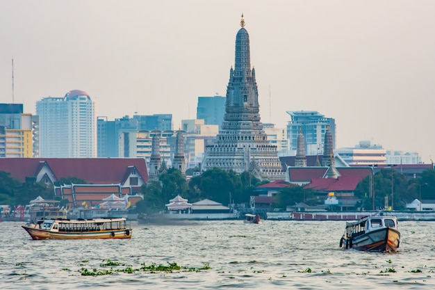 Boat in the chao phraya river and wat arun