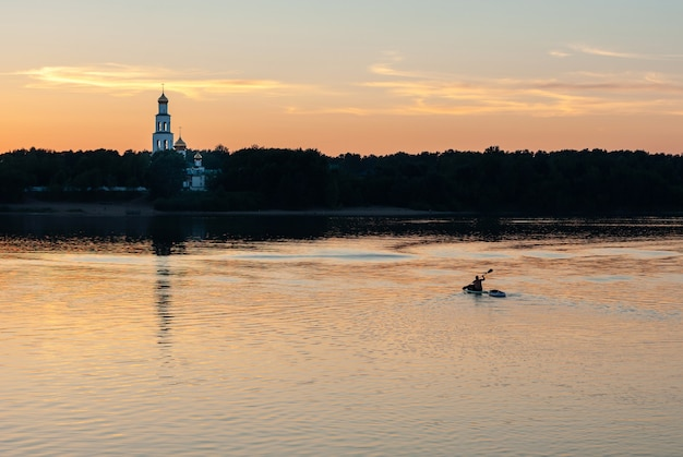 Boat crossing river at sunset, with small white church on the other side
