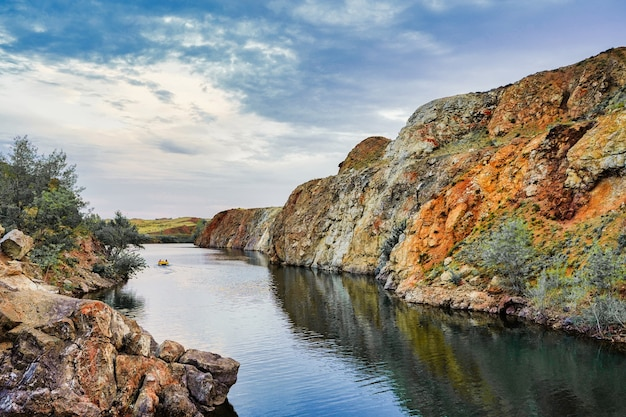 Катание на лодке по реке вдалеке озеро в каньоне осенью завораживающие пейзажные обои