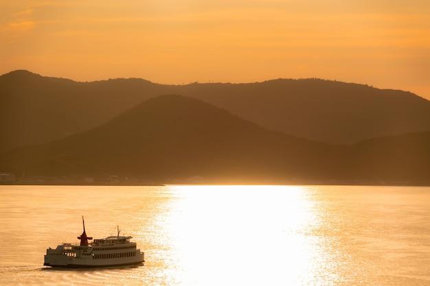 보트 페리는 일본의 다카마쓰 섬을 따라 여행하며 휴가 및 일본 여행 컨셉을위한 황금빛 일몰 반사 하늘이 있습니다.