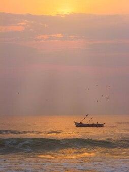 日の出の光で海でのボート釣り